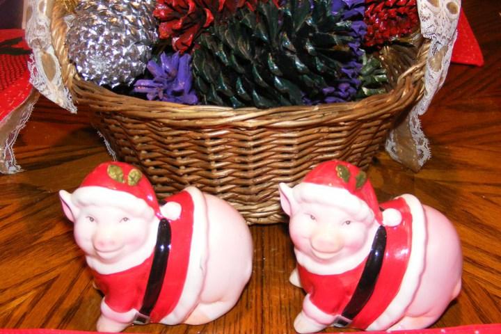 фигурки новогодних поросят рядом с корзиной с шишками