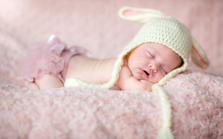 Новорожденная девочка в смешной шапке