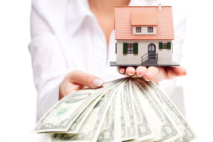 Девушка держит в руках макет дома и деньги