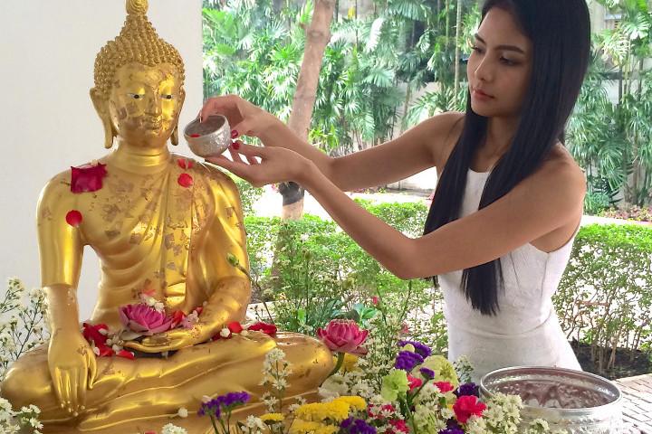 девушка поливает статую будды