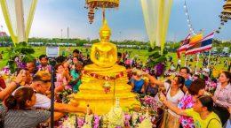 люди поливают статую будды