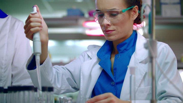 женщина химик в защитных очках и халате