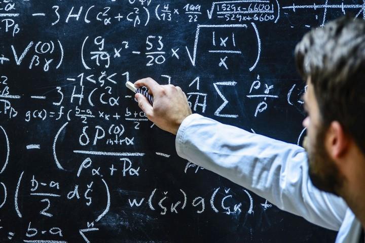 учитель пишет на доске уравнения