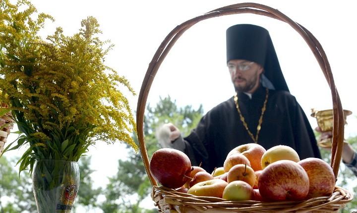 корзина с яблоками и букет мимозы на фоне священника