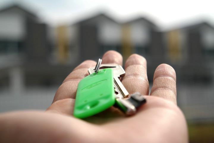 рука с ключами на фоне многоквартирных домов