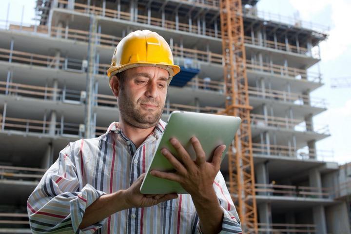 строитель на фоне строящегося дома