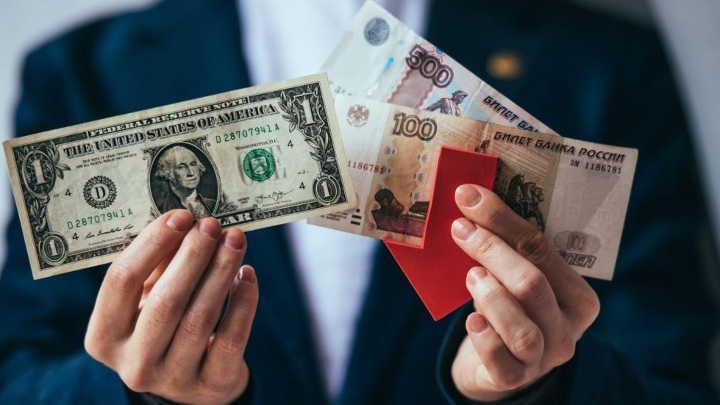 в руках мужчины доллар и рубли