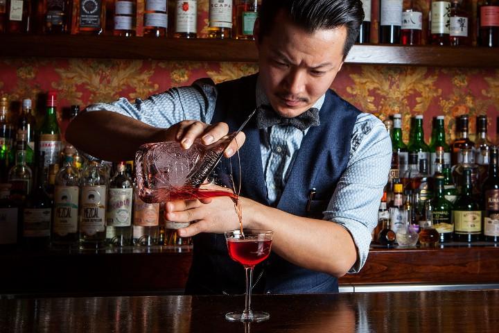 бармен наполняет бокал