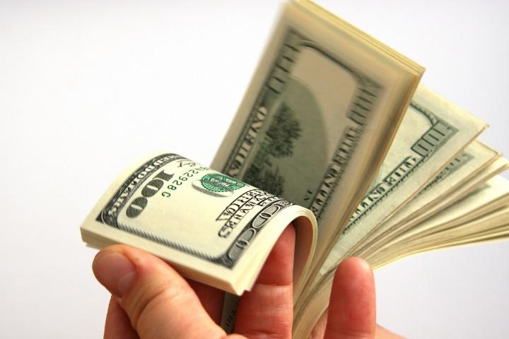 пачка долларов в руке