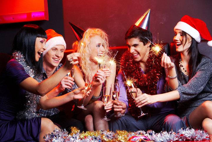 молодые люди с шампанским в руках за новогодним столом