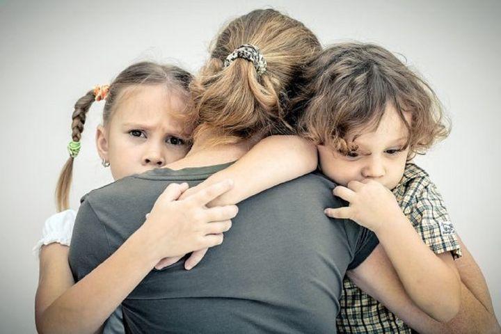 Двое детей обнимают маму