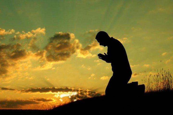 мужчина молится на рассвете