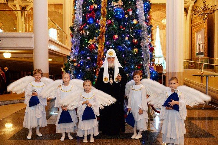 святой отец и дети в костюмах около елки в храме спасителя