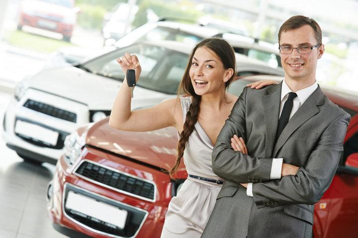 семейная пара с ключами на фоне автомобилей