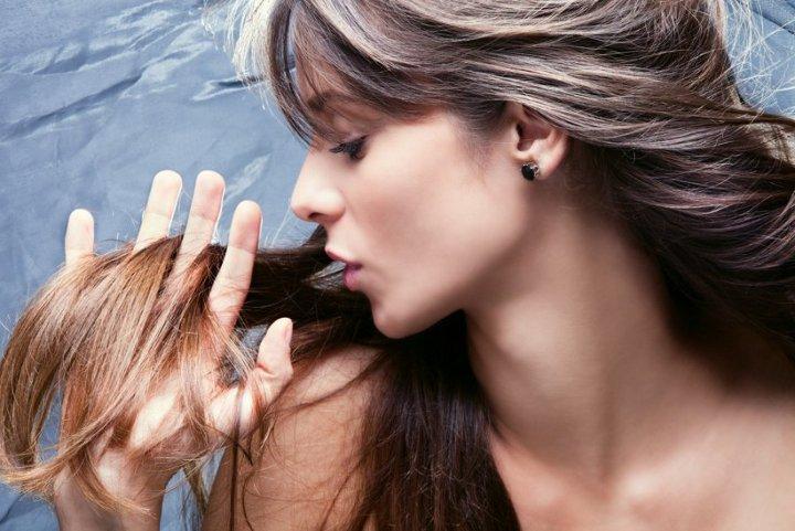 девушка проводит рукой по волосам