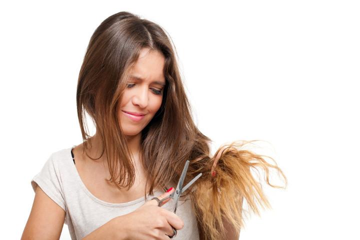 девушка стрижет себе волосы