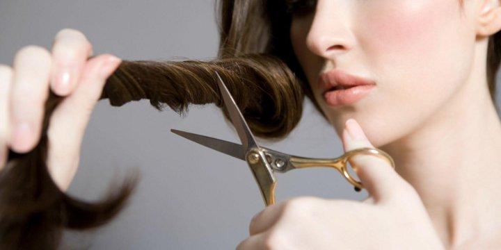 девушка обрезает себе волосы