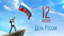 мужчина на скале с флагом россии в руках
