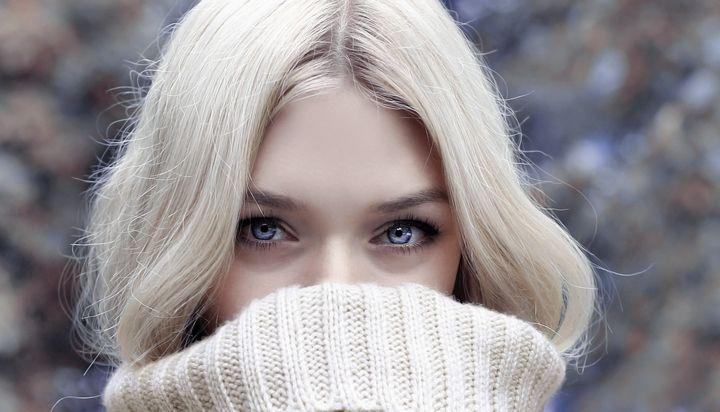 Девушка прячет лицо в шарф
