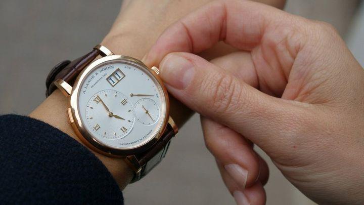 Мужчина переводит часы