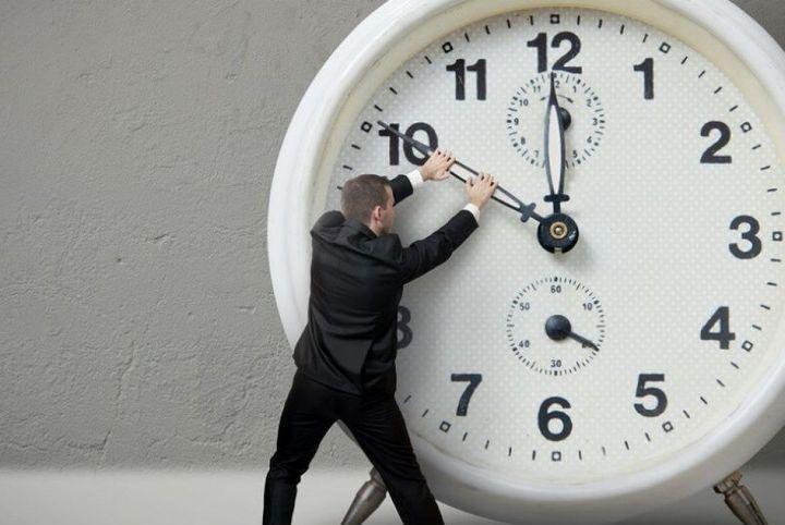 Мужчина переводит стрелки часов