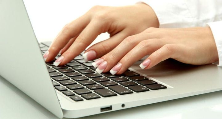 Девушка печатает текст на клавиатуре
