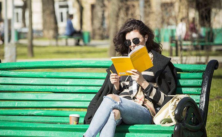 Девушка в парке читает книгу
