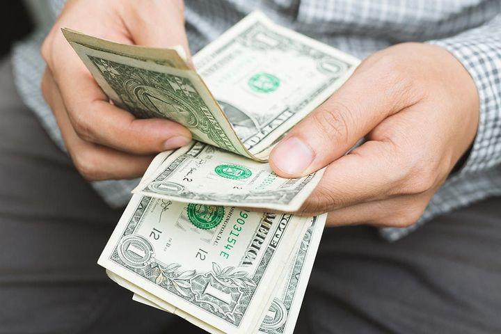 Мужчина считает доллары