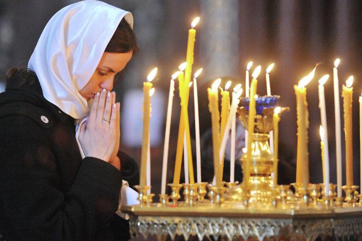 девушка ставит свечку и молится