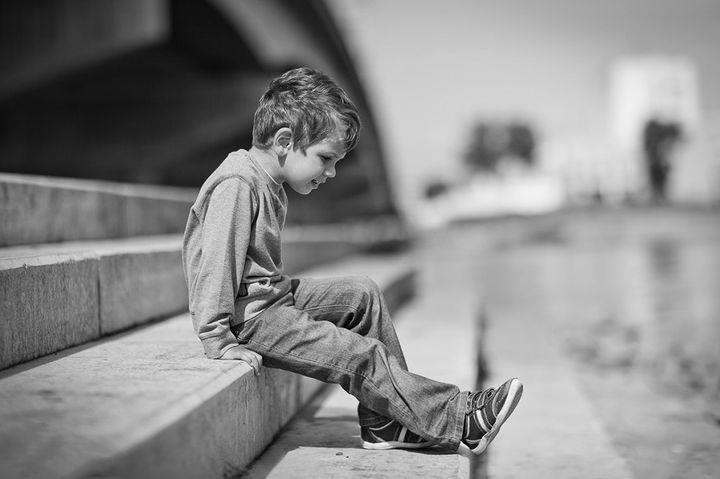 Мальчик сидит на ступеньках