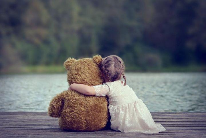 Девочка обнимает мишку